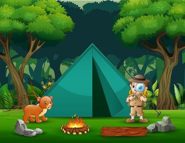 O menino explorador acampando na floresta