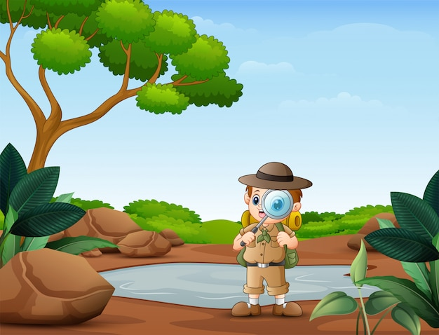 O menino explorador com lupa na natureza