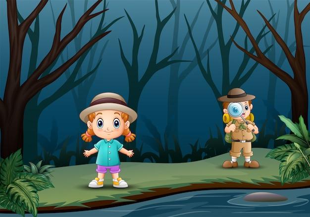 O menino explorador com uma garotinha na floresta seca