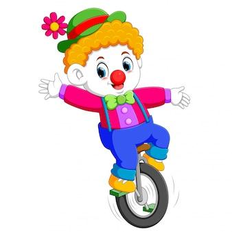 O menino usa o traje de circo e em pé no monociclo