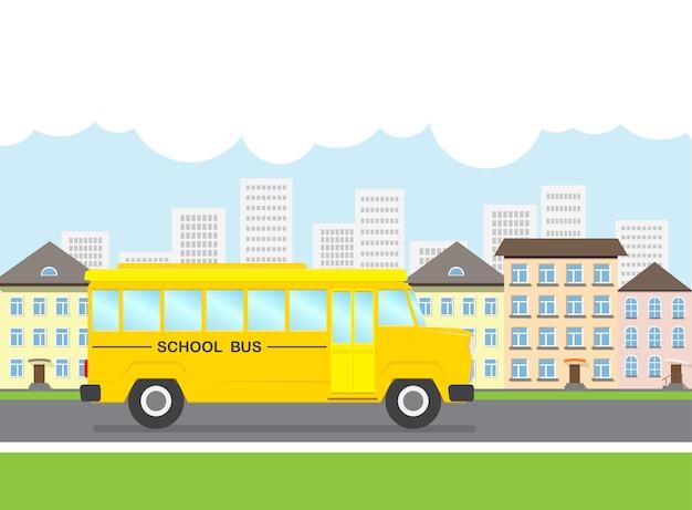 O ônibus escolar passa pela rua tendo como pano de fundo a cidade