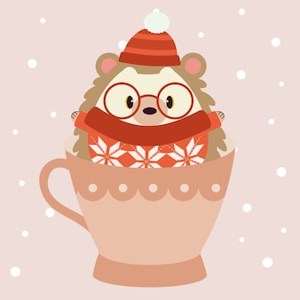 O personagem de ouriço fofo usa um chapéu vermelho de inverno, óculos grandes e blusa vermelha e sentado no grande copo rosa