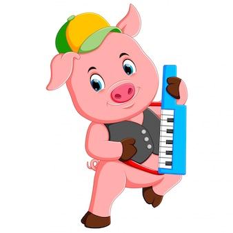 O porco rosa usa o boné amarelo e cinza tocando piano