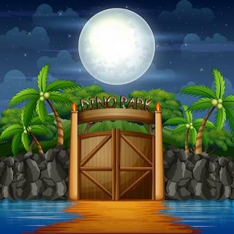O portão do parque dino na paisagem noturna
