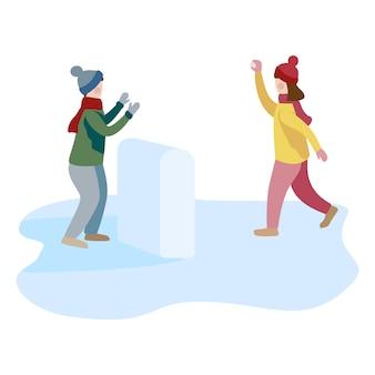 O rapaz pequeno e a menina que jogam a bola de neve lutam e que têm o divertimento na neve no inverno.