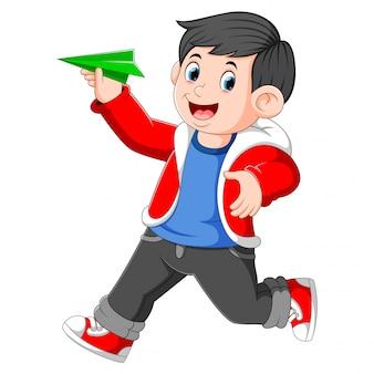 O rapaz usando o casaco vermelho está segurando o avião de papel verde