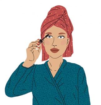 O rímel de tinta para olhos de mulher bonita saiu do chuveiro com uma toalha na cabeça e um roupão macio. conceito de cuidar de seu corpo e imagem. amor por si mesmo, maquiagem, blogueiro de maquiagem.