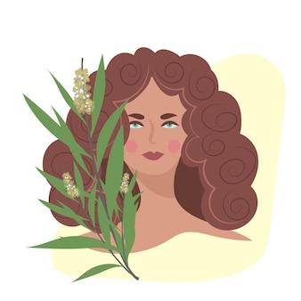O rosto de uma jovem com o galho de uma árvore do chá em flor