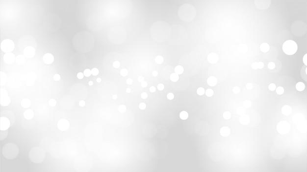 O sumário borrão o fundo branco e cinzento da cor com as luzes brancas do bokeh defocused.