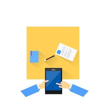 O telefone funciona em uma mesa com caneta e caderno.