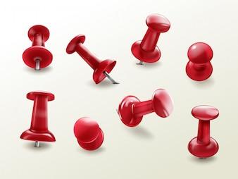 O thumbtack do escritório dos artigos de papelaria, jogo realístico de pinos lustrosos vermelhos do impulso para fixar na placa lembra