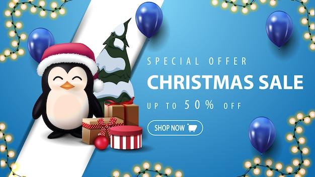 Oferta especial, liquidação de natal, banner azul de desconto com guirlanda, balões azuis, linha diagonal e pinguim com chapéu de papai noel com presentes