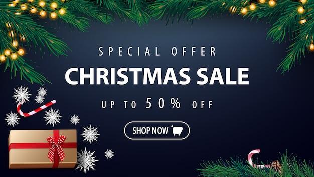 Oferta especial, venda de natal, desconto de até 50%, banner de desconto azul com guirlanda, árvore de natal, presente, flocos de neve de papel e lata de doces, vista superior