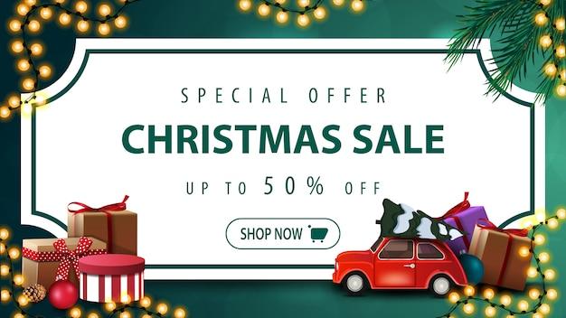 Oferta especial, venda de natal, desconto de até 50%, banner de desconto verde com folha de papel branco em forma de bilhete vintage, galhos de árvores de natal, guirlandas e carro antigo vermelho com árvore de natal