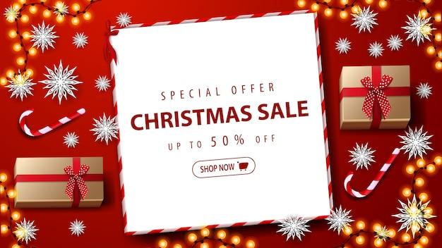 Oferta especial, venda de natal, descontos de até 50%. banner de desconto vermelho com presentes, pirulito, flocos de neve de papel, guirlanda e folha de papel branco com oferta na mesa vermelha, vista superior