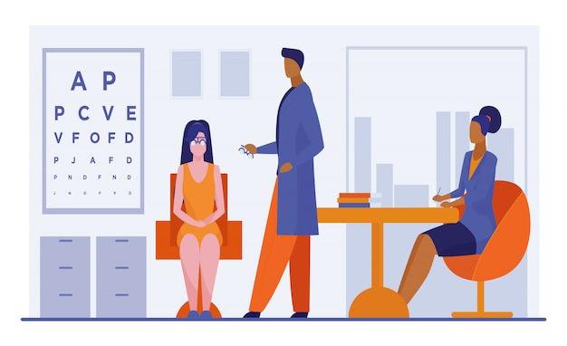 Oftalmologista e enfermeira que verificam a visão da mulher