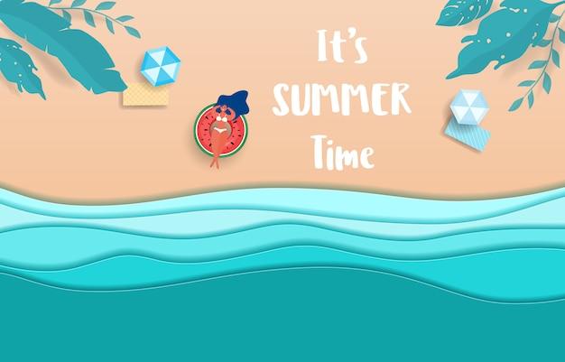Ondas de papel e praia. a menina quente no anel de borracha toma sol na temporada de verão.