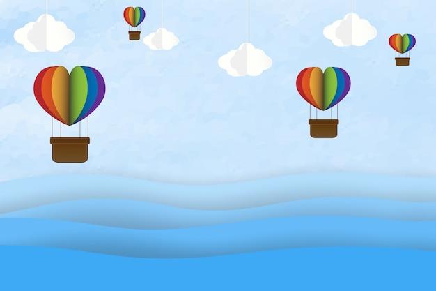 Origami fez o balão de ar quente colorido em um coração com forma pendurar no céu