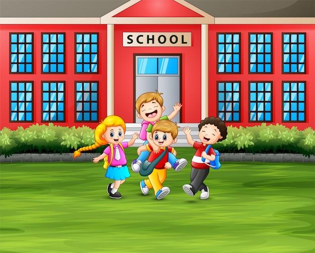 Os alunos com mochilas na frente do prédio da escola