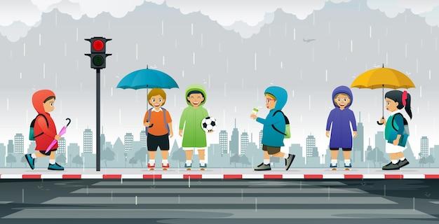 Os alunos vestem capas de chuva e seguram guarda-chuvas à espera do semáforo para atravessar a faixa de pedestres