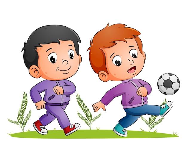 Os dois meninos estão jogando futebol e chutando a bola no campo de ilustração