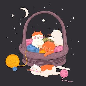 Os gatinhos dormem em uma cesta com bolas de fios.