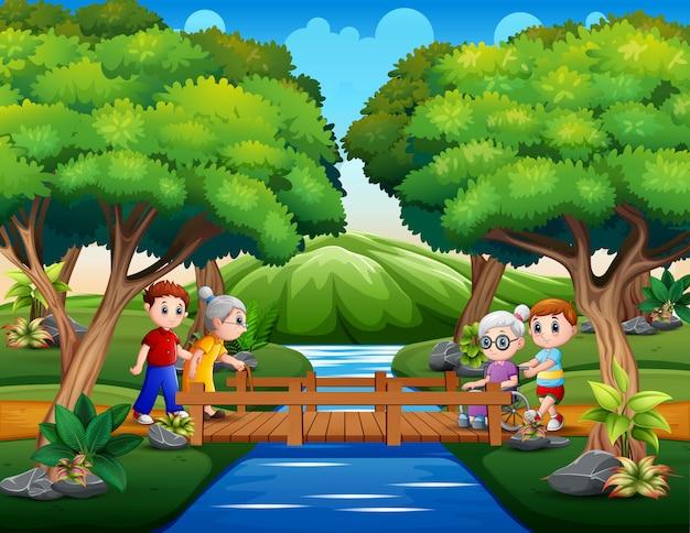 Os idosos com seu neto através da ponte de madeira