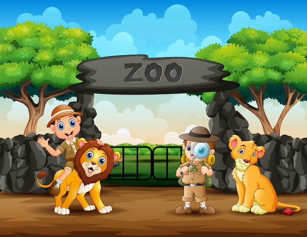 Os meninos do tratador e animais selvagens no zoológico