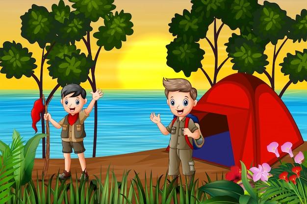 Os meninos escoteiros acampar à beira do lago ao pôr do sol