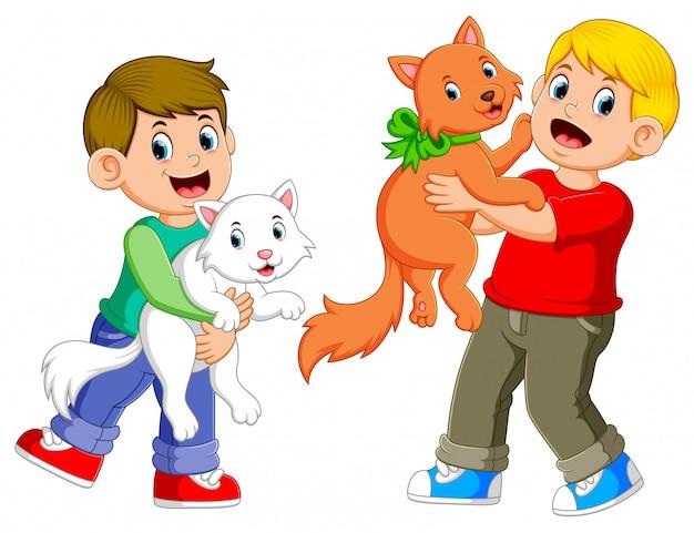 Os meninos estão brincando com seus gatos com o rosto feliz