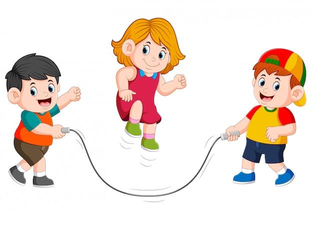 Os meninos estão jogando a corda de salto com a menina pulando sobre ele