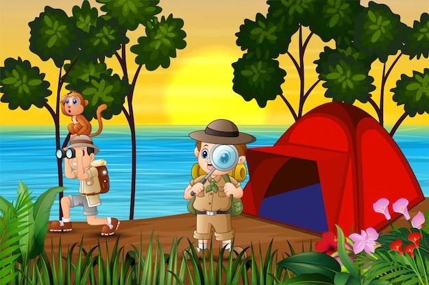 Os meninos exploradores acampar à beira do lago ao pôr do sol