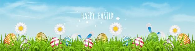 Os ovos da páscoa coloridos alinham e florescem flores na grama com céu bonito.