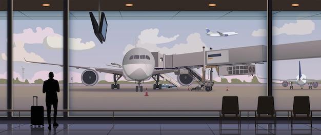 Os passageiros esperam para embarcar no avião no terminal.