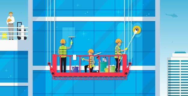 Os trabalhadores estão limpando o edifício de vidro com um guindaste seguro