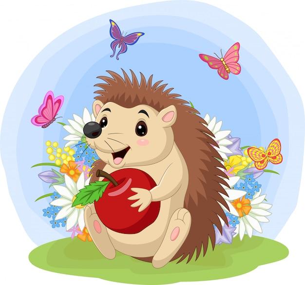 Ouriço de bebê dos desenhos animados, segurando a maçã na grama