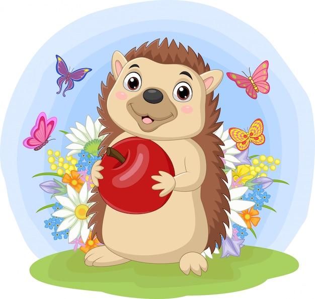 Ouriço dos desenhos animados, segurando a maçã na grama