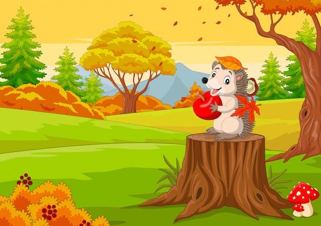 Ouriço dos desenhos animados, segurando a maçã vermelha na floresta de outono