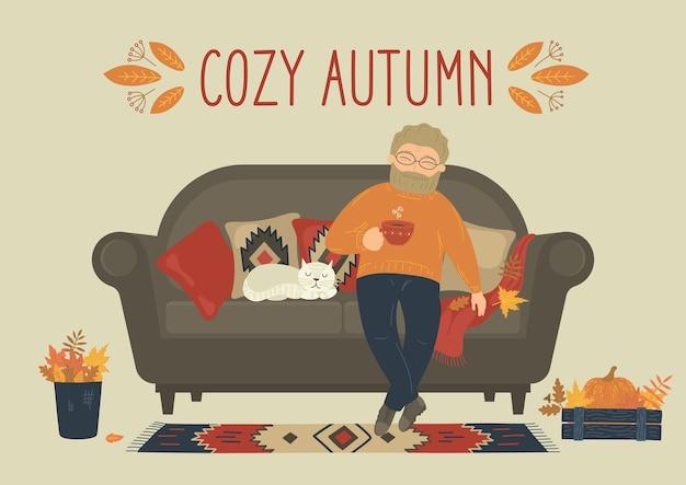 Outono aconchegante. homem bebe chá ou café no sofá em casa.