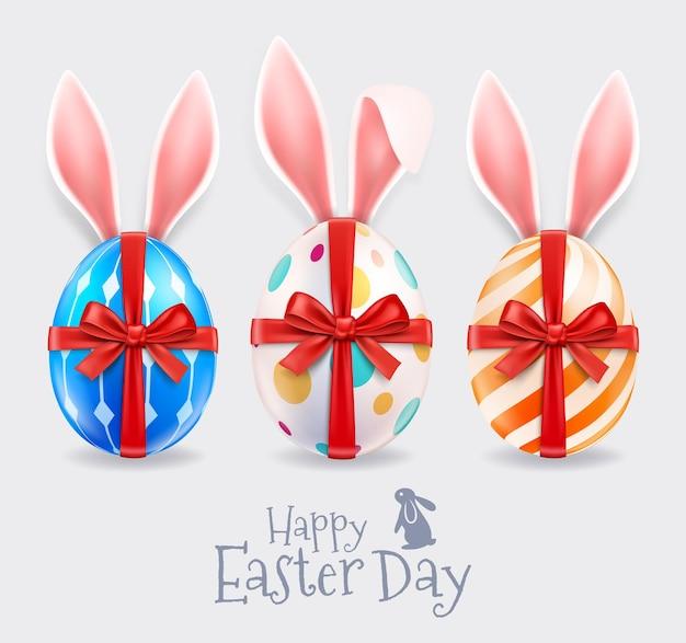Ovos de páscoa e orelhas de coelho com fita vermelha.