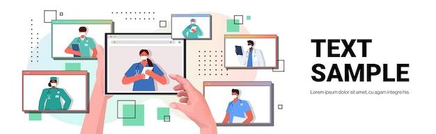 Paciente discutindo com médicos de raça mista nas janelas do navegador da web durante consulta médica online por videochamada