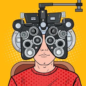 Paciente pop art man na clínica optométrica com phoropter óptico