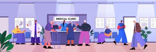 Pacientes idosos visitando recepcionista de consultório de clínica médica dando informações para idosos na recepção