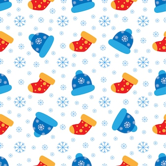 Padrão bonito com bonés de inverno e flocos de neve.