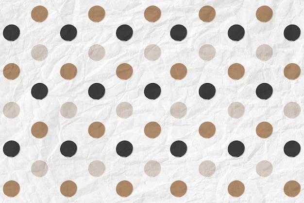 Padrão de bolinhas em preto e dourado em plano de fundo texturizado de papel amassado