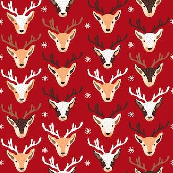 Padrão de natal festivo sem costura com cabeças de renas e enfeites em vetor de fundo vermelho ...