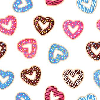 Padrão sem emenda com donuts em forma de coração com glacê rosa, azul e chocolate.