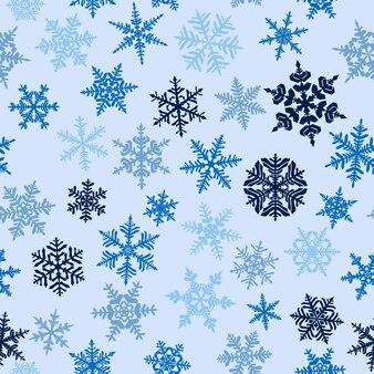 Padrão sem emenda de natal com flocos de neve complexos grandes e pequenos, coloridos em fundo azul claro