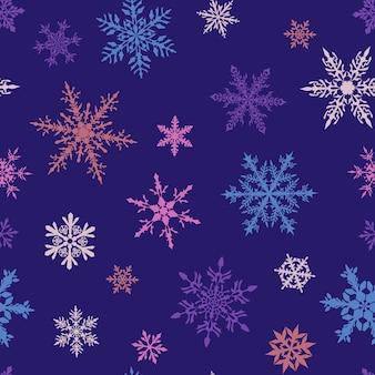Padrão sem emenda de natal de complexos grandes e pequenos de flocos de neve multicoloridos sobre fundo azul
