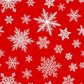 Padrão sem emenda de natal de flocos de neve complexos grandes e pequenos em cores brancas sobre fundo vermelho